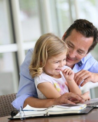 Father and daughter looking at internet on laptop